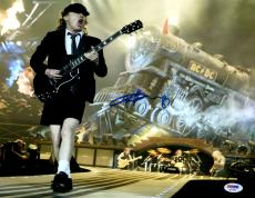 """Angus Young Autographed 11"""" x 14""""  AC/DC Playing Guitar With Train In Background Photograph - PSA/DNA COA"""