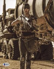 """Charlize Theron Autographed 8"""" x 10"""" Mad Max Holding Gun Photograph - Beckett COA"""