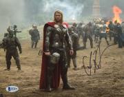 "Chris Hemsworth Autographed 8"" x 10"" Thor: Standing in Battlefield Photograph - Beckett COA"
