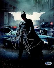 "Christian Bale Autographed 8"" x 10"" The Dark Knight Rises Batman Standing in Street with Police & White Batman Symbol in Background Photograph - Beckett COA"