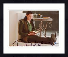 "Framed Tom Hiddleston Autographed 8"" x 10"" Thor Sitting on Floor Reading Book Photograph - Beckett COA"