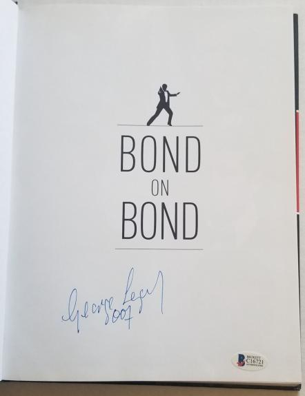 George Lazenby Signed 007 50 Years Of James Bond Hard Cover Book Beckett BAS COA