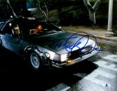 "Michael J Fox Autographed 11"" x 14"" Back To The Future Sitting In The Delorean Photograph - Beckett COA"