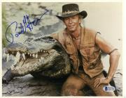 "Paul Hogan Autographed 8""x 10"" Crocodile Dundee Sitting Next To Crocodile Photograph - Beckett COA"