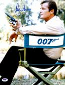 """Roger Moore Autographed 11"""" x 14"""" James Bond Sitting in 007 Chair Holding Gun Photograph - PSA/DNA COA"""