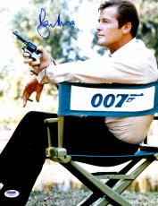 "Roger Moore Autographed 11"" x 14"" James Bond Sitting in 007 Chair Holding Gun Photograph - PSA/DNA COA"