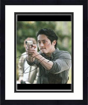 Steven Yeun Autographed The Walking Dead 8X10 Photo (w/gun)