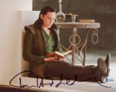 "Tom Hiddleston Autographed 8"" x 10"" Thor Sitting on Floor Reading Book Photograph - Beckett COA"
