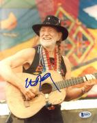 "Willie Nelson Autographed 8"" x 10"" Playing Guitar With Colorful Flag in Background Photograph - Beckett COA"
